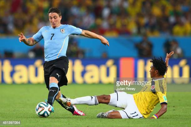 Juan Guillermo Cuadrado of Colombia tackles Cristian Rodriguez of Uruguay during the 2014 FIFA World Cup Brazil round of 16 match between Colombia...