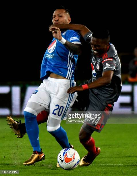 Juan Guillermo Dominguez of Millonarios vies for the ball with Ivan Velez of America de Cali during the friendly match between Millonarios and...