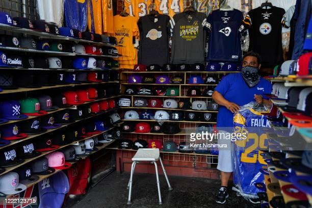 Juan Hernandez hangs jerseys at his vendor stall at the Santa Fe Springs Swap Meet where he sells licensed merchandise on Saturday, June 20, 2020 in...