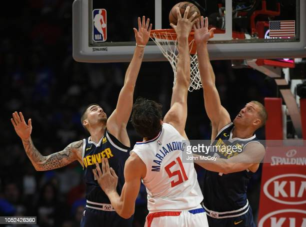 Juan Hernangomez of the Denver Nuggets and Mason Plumlee of the Denver Nuggets can not stop Boban Marjanovic of the LA Clippers from dunking the ball...