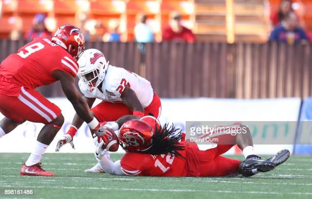Juan Hines of the Houston Cougars intercepts a pass as he falls to the ground during the first quarter of the Hawaii Bowl against the Fresno State...