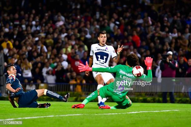 Juan Ignacio Dinenno of Pumas kicks the ball to score the third goal of his team against Guillermo Ochoa of America during the 9th round match...