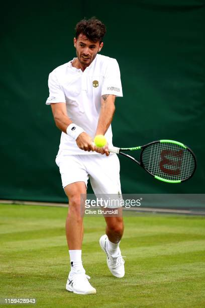 Juan Ignacio Londero of Argentina plays a backhand in his Men's Singles first round match against Benoit Paire of France during Day one of The...