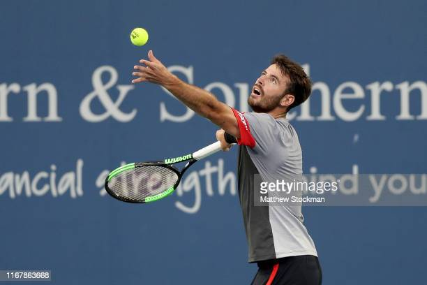 Juan Ignacio Londero of Argentina serves to Roger Federer of Switzerland during the Western Southern Open at Lindner Family Tennis Center on August...