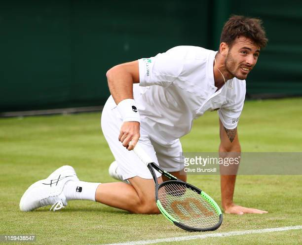 Juan Ignacio Londero of Argentina slips over in his Men's Singles first round match against Benoit Paire of France during Day one of The...