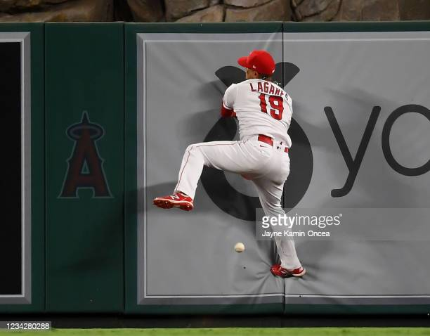 Juan Lagares of the Los Angeles Angels crashes into the wall as he leaps for a two run double hit by Raimel Tapia of the Colorado Rockies in the...
