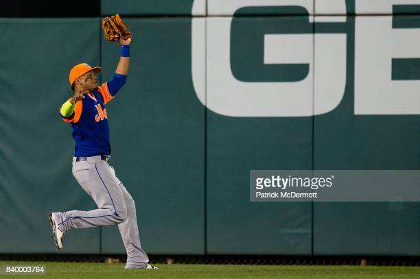 Juan Lagares of the New York Mets catches a sacrifice fly ball hit by Adam Lind of the Washington Nationals in the fourth inning during Game Two of a...