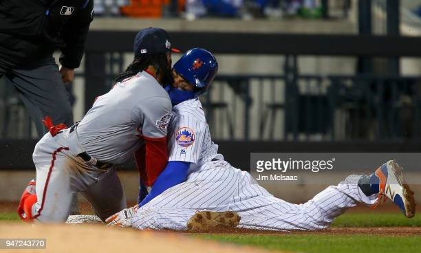 Juan Lagares of the New York Mets collides with Wilmer Difo of the Washington Nationals as he steals third base during the sixth inning at Citi Field...