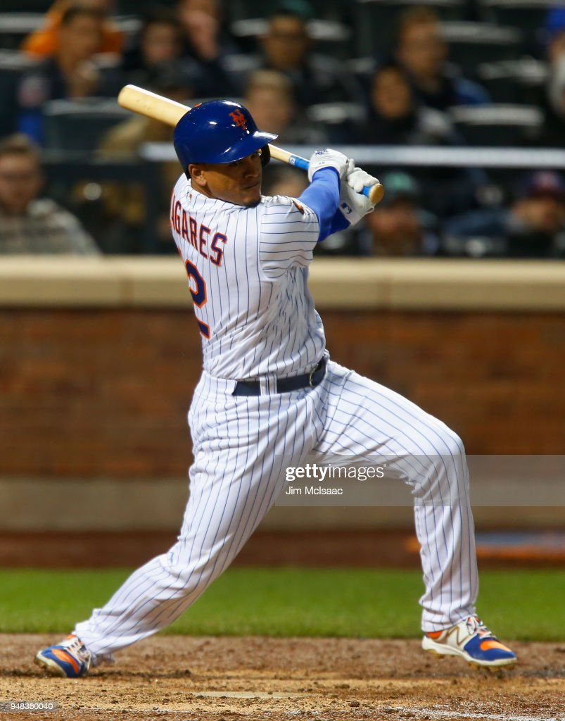 Juan Lagares #12 of the New York Mets follows through on an eighth inning two run double against the Washington Nationals at Citi Field on April 18, 2018 in the Flushing neighborhood of the Queens borough of New York City.