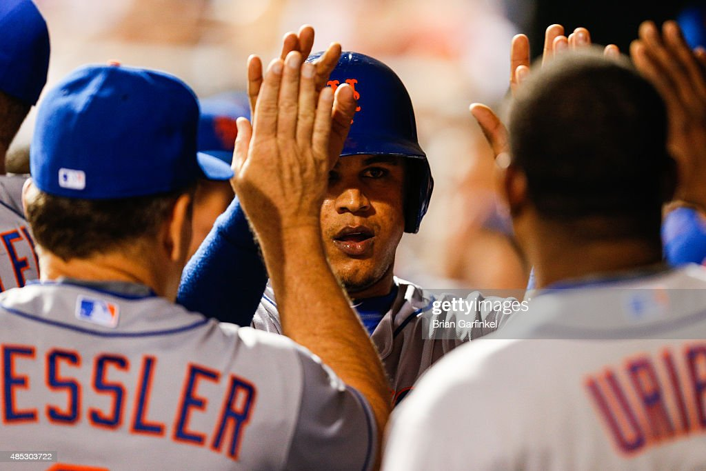 Juan Lagares #12 of the New York Mets high-fives teammates in the dugout after scoring a run in the ninth inning of the game against the Philadelphia Phillies at Citizens Bank Park on August 26, 2015 in Philadelphia, Pennsylvania. The Mets won 9-4.