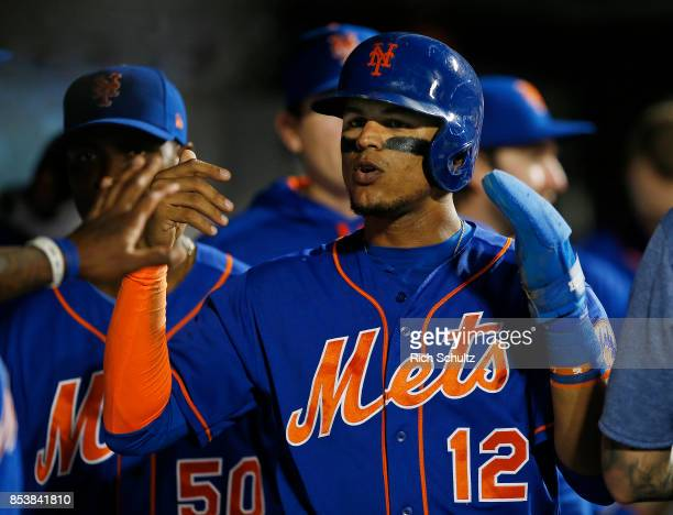 Juan Lagares of the New York Mets is congratulated after scoring on a double by Travis d'Arnaud in the third inning against the Atlanta Braves during...