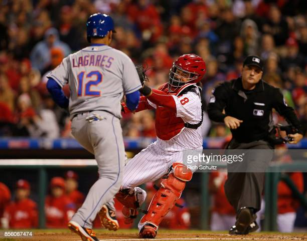 Juan Lagares of the New York Mets is tagged out by catcher Jorge Alfaro of the Philadelphia Phillies who attempted to score on a flyable by Travis...