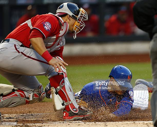 Juan Lagares of the New York Mets is tagged out by catcher Wilson Ramos of the Washington Nationals on a single by Lucas Duda in the first inning on...