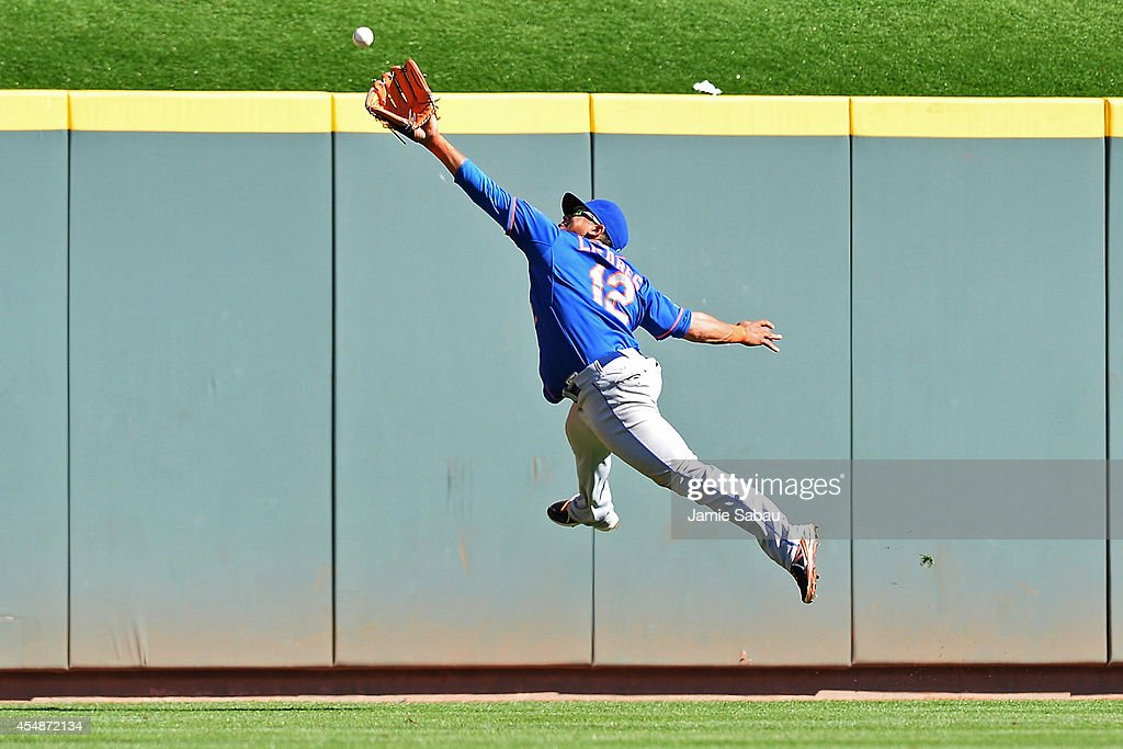 Juan Lagares #12 of the New York Mets makes a leaping attempt to catch a ball hit by Jack Hannahan #9 of the Cincinnati Reds in the ninth inning at Great American Ball Park on September 7, 2014 in Cincinnati, Ohio. Hannahan was credited with a double as New York defeated Cincinnati 4-3.