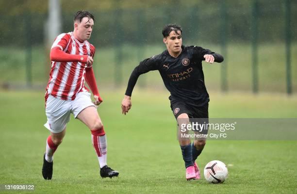 Juan Larios of Manchester City runs past Josh Ireland of Stoke City during the U18 Premier League match between Stoke City and Manchester City at...