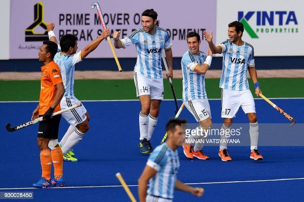 Juan Lopez of Argentina celebrates with teammates after scoring a goal against Malaysia during their men's field hockey thirdfourth place match of...