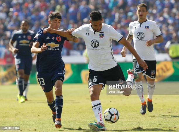 Juan Manuel Insaurralde of Colo Colo fights for the ball with Angelo Araos of U de Chileduring a match between U de Chile and Colo Colo as part of...