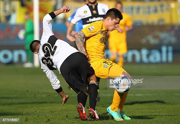 Juan Manuel Iturbe of Hellas Verona FC competes with Marco Marchionni of Parma FC during the Serie A match between Parma FC and Hellas Verona FC at...