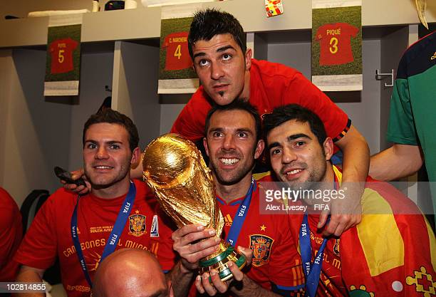 Juan Manuel Mata Carlos Marchena David Villa and Raul Albiol pose with the trophy in the Spanish dressing room after they won the 2010 FIFA World Cup...