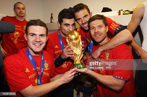 Juan Manuel Mata Raul Albiol Carlos Marchena and Xabi Alonso pose with the trophy in the Spanish dressing room after they won the 2010 FIFA World Cup...