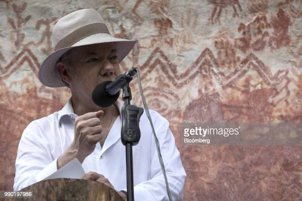 Juan Manuel Santos Colombia's president speaks in front of a wall of rock art during a tour of the Chiribiquete National Park near San Jose del...