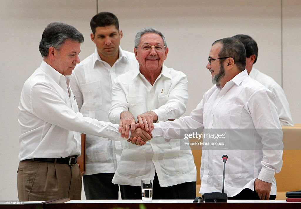 Juan Manuel Santos, president of Colombia (L), Raul Castro, President of Cuba (C) and Rodrigo Londoño, known as 'Timoshenko', top leader of the Revolutionary Armed Forces of Colombia (FARC) , shake hands during a meeting about transitional justice agreement on September 23, 2015 in Havana, Cuba. The agreement contemplates an amnesty for political crimes, the creation of a special court for peace, and states that the guerrillas must surrender their weapons within 60 days after signing the final agreement.