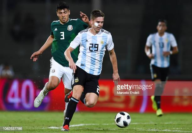 Juan Marcos Foyth of Argentina drives the ball against Érick Gutiérrez during a friendly match between Argentina and Mexico at Mario Kempes Stadium...