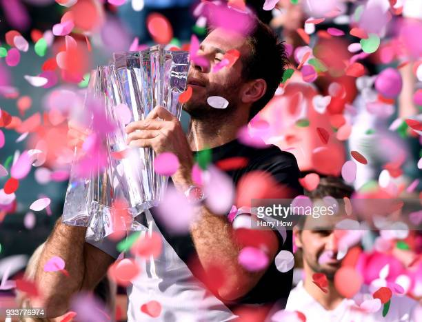 Juan Martin Del Potro of Argentina holds up the trophy in front of Roger Federer of Switzerland after his victory in the ATP final during the BNP...
