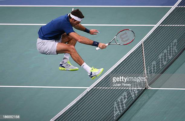 Juan Martin Del Potro of Argentina jumps the net after failing to make a shot in his match against Roger Federer of Switzerland during day five of...