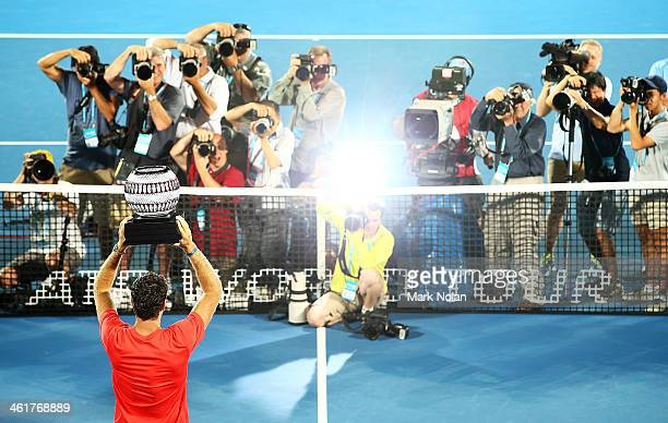 Juan Martin Del Potro of Argentina poses for photos with the trophy after winning the Mens Single Final against Bernard Tomic of Australia during day...