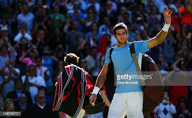 Juan Martin Del Potro of Argentina waves to fans as he walks off the court after losing 4-6, 7-6, 19-17 to Roger Federer of Switzerland in the...