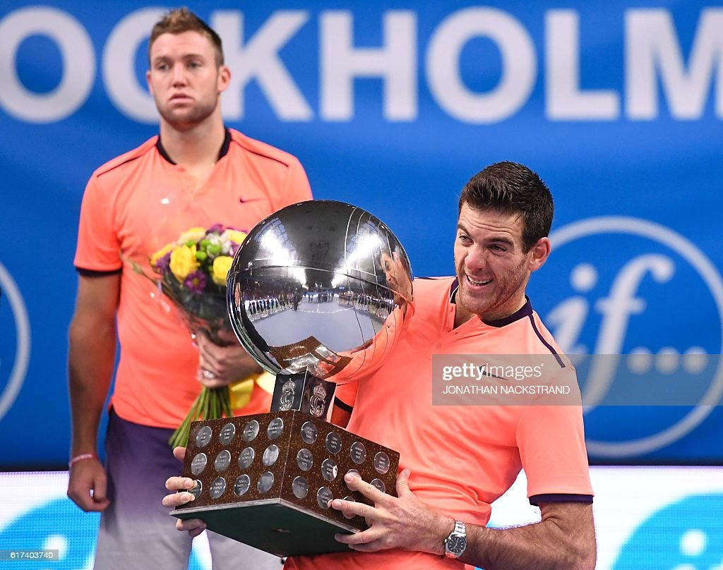 Juan Martin Del Potro reacts as he lifts the heavy trophy during an award ceremony after defeating USA's Jack Sock at the ATP Stockholm Open tennis tournament final match on October 23, 2016 in Stockholm. / AFP / JONATHAN