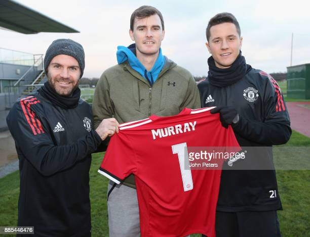 Juan Mata and Ander Herrera of Manchester United pose with tennis player Jamie Murray ahead of a first team training session at Aon Training Complex...