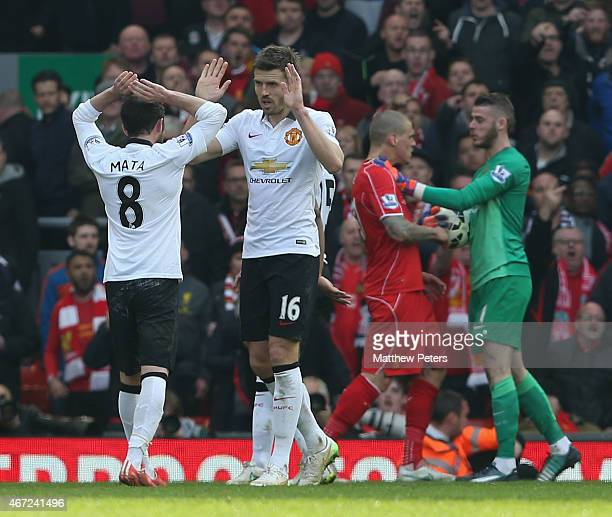 Juan Mata and Michael Carrick of Manchester United celebrate as David de Gea and Martin Skrtel of Liverpool clash after the Barclays Premier League...