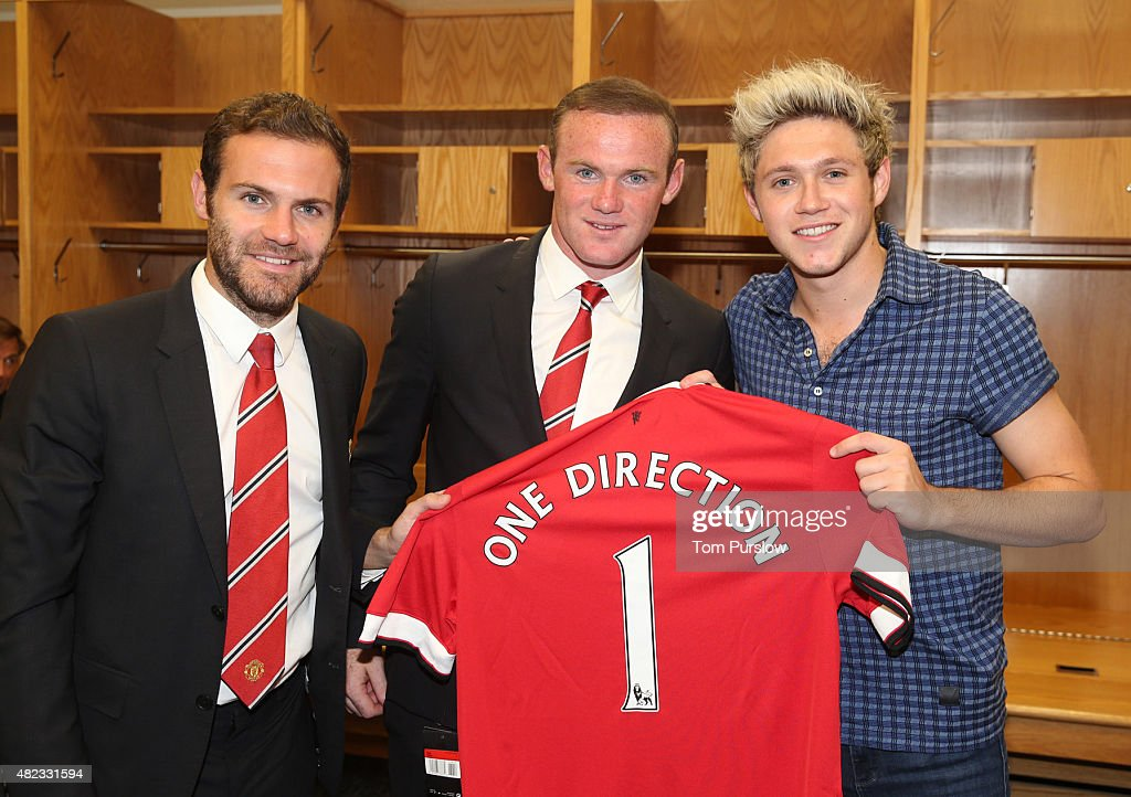 (MINIMUM PRINT/BROADCAST FEE OF GBP 150, ONLINE FEE OF GBP 50 PER IMAGE, OR LOCAL EQUIVALENT) Juan Mata and Wayne Rooney of Manchester United pose with Niall Horan of pop group One Direction after the International Champions Cup 2015 match between Manchester United and Paris Saint Germain at Soldier Field on July 29, 2015 in Chicago, Illinois.
