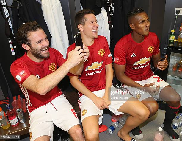 Juan Mata Ander Herrera and Antonio Valencia of Manchester United share a joke in the dressing room after the FA Community Shield match between...