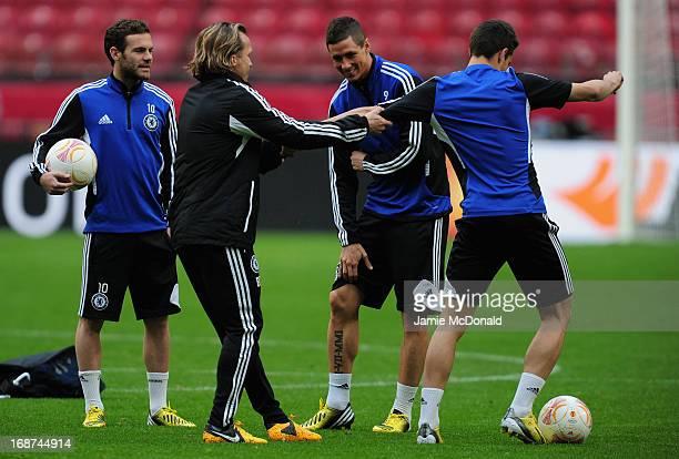 Juan Mata looks on as assistant Boudewijn Zenden shares a joke with Fernando Torres and Cesar Azpilicueta of Chelsea during a Chelsea training...