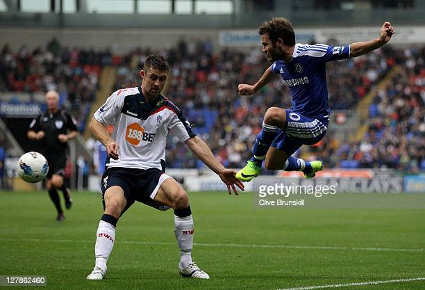 Juan Mata of Chelsea shoots past Gary Cahill of Bolton Wanderers during the Barclays Premier League match between Bolton Wanderers and Chelsea at the...