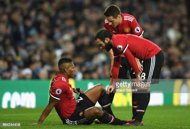 Juan Mata of Manchester United and Ander Herrera check on Antonio Valencia of Manchester United after he goes down injured during the Premier League...