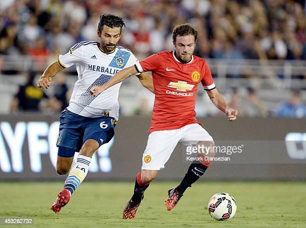 Juan Mata of Manchester United and Baggio Husidic of Los Angeles Galaxy during the preseason friendly match at the Rose Bowl in Pasadena California...