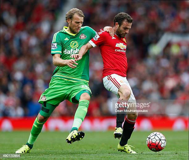 Juan Mata of Manchester United and Ola Toivonen of Sunderland compete for the ball during the Barclays Premier League match between Manchester United...