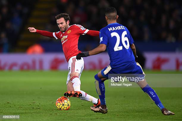 Juan Mata of Manchester United and Riyad Mahrez of Leicester City compete for the ball during the Barclays Premier League match between Leicester...
