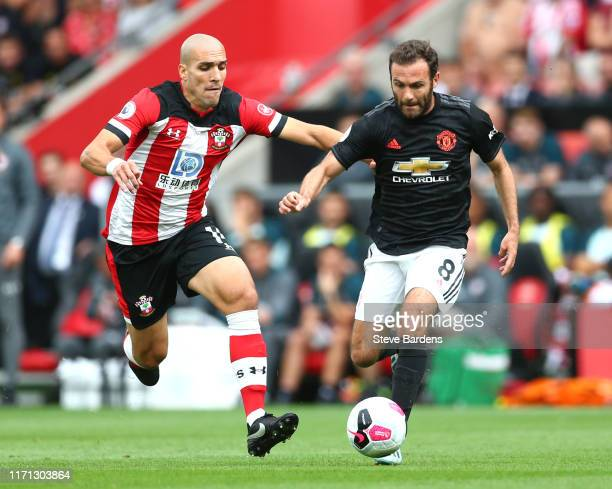 Juan Mata of Manchester United battles for possession with Oriol Romeu of Southampton during the Premier League match between Southampton FC and...