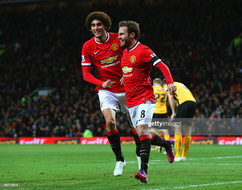 Juan Mata of Manchester United celebrates scoring the opening goal with Marouane Fellaini of Manchester United during the FA Cup Fourth round replay match between Manchester United and Cambridge United at Old Trafford on February 3, 2015 in Manchester, England.