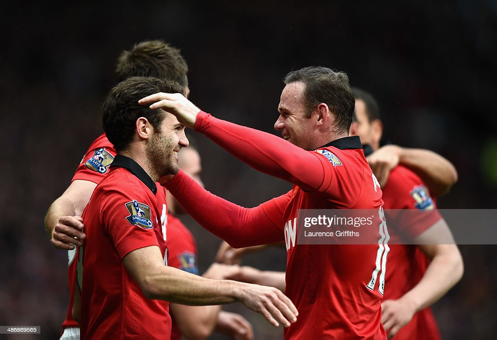 Juan Mata of Manchester United celebrates the fourth goal with Wayne Rooney during the Barclays Premier League match between Manchester United and Norwich City at Old Trafford on April 26, 2014 in Manchester, England.
