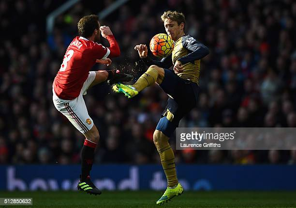 Juan Mata of Manchester United challenges Nacho Monreal of Arsenal during the Barclays Premier League match between Manchester United and Arsenal at...