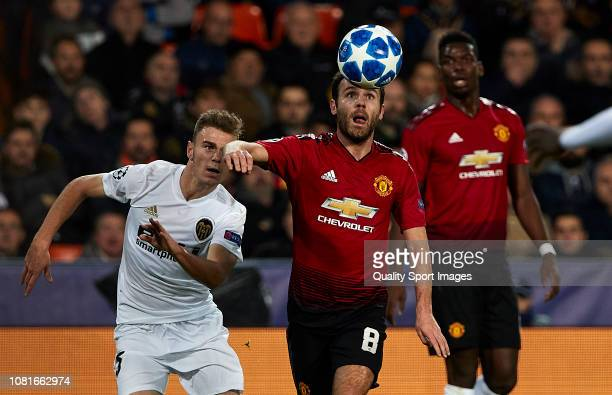 Juan Mata of Manchester United challenges the ball with Antonio Latorre Lato of Valencia CF during the UEFA Champions League Group H match between...