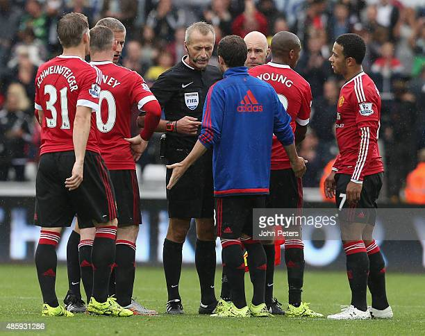 Juan Mata of Manchester United complains to referee Martin Atkinson after the Barclays Premier League match between Swansea City and Manchester...
