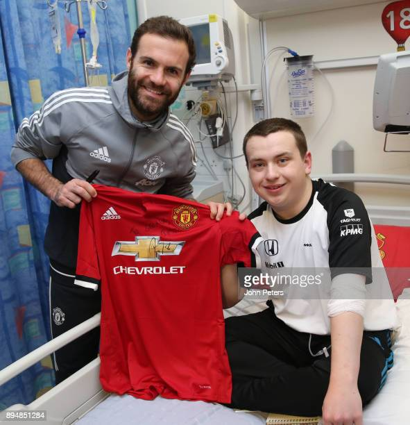 Juan Mata of Manchester United delivers Christmas presents to George 15 from Stockport during the club's annual Christmas hospital visits at Royal...
