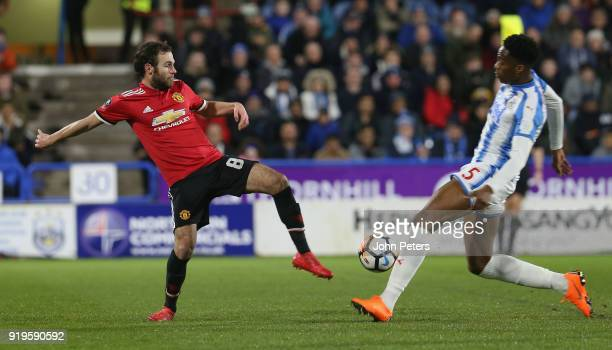 Juan Mata of Manchester United in action with Terence Kongolo of Huddersfield Town during the Emirates FA Cup Fifth Round match between Huddersfield...